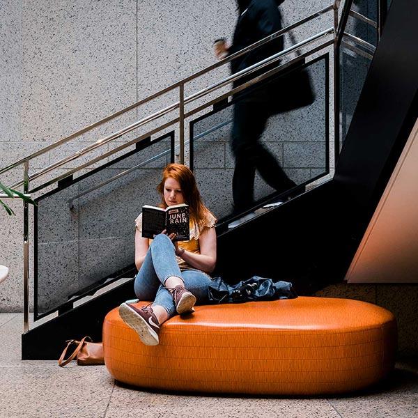 girl reading on orange cushion